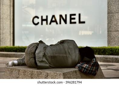 SEOUL, KOREA - SEPTEMBER 16, 2015: Homeless man sleeping in front of luxury store