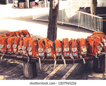 Seoul, Korea - September 18, 2018 : The orange school bag of primary student arange in row on the wooden bench that go to Everland fun park