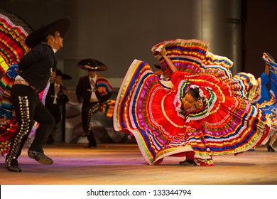 Seoul, Korea - September 30, 2009: Female Mexican Jalisco dancer bent over in fluttering orange dress spinning, twirling at a folkloric dance outdoor free performance in Seoul, South Korea
