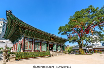 SEOUL, KOREA-SEPTEMBER 27, 2107: Famous Jogyesa Temple and decorated Chinese Scholar Tree. Sign translated: Daeungjeon - Main Dharma Hall. Three is believed to be over 450 years old.