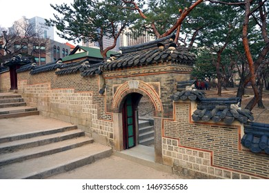 Seoul - March 2019: Small gate and stone wall of the palace building. Deoksugung Palace, Seoul.