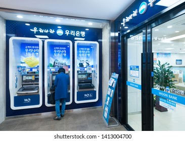 SEOUL - MARCH 29, 2017: An unidentified woman stands by a Woori Bank ATM at the Hyundai IPark shopping mall. Woori Bank is a subsidiary of the parent company Woori Financial Group.