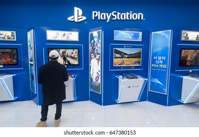 SEOUL - MARCH 29, 2017: A young man uses a PS4 at the Hyundai IPark shopping mall. PlayStation 4 (PS4) is a line of home video game consoles developed by Sony Interactive Entertainment.