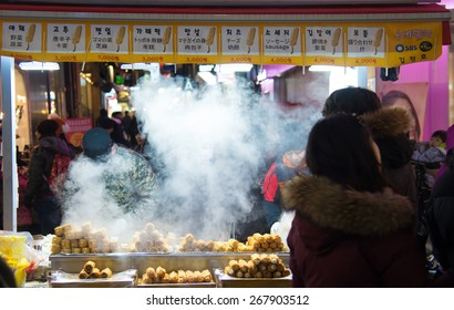 Seoul, Republic of Korea - January 1, 2015 : Traditional Korean street food market scene with white smoke at Myeongdong district ,famous shopping street, at night  in Seoul capital of South Korea.