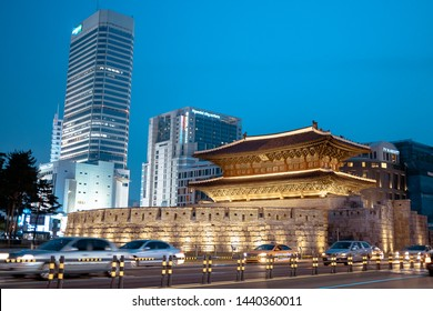 Seoul, South Korea - 08.05.18:Dongdaemun gate night landscape against the background of skyscrapers, rear view. Dongdemun gate among modern buildings in the evening