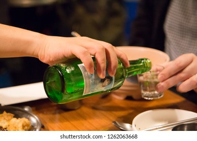 Seoul, South Korea - 1 December 2018: soju pouring from bottle into glass at the party in korea