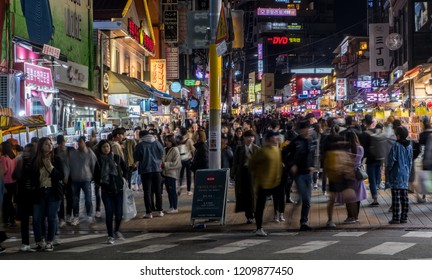 Seoul / South Korea - 12 Oct 2018: Hongyik University, Hongdae, street shopping crowds at night with motion blur to show the movement of the crowds