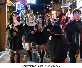 Seoul, South Korea - 27 October 2019: Youung women disguised as nurse celebrate Halloween in the street of Itaewon in Seoul international district