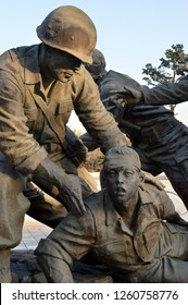"SEOUL, SOUTH KOREA - 30 NOVEMBER 2018: Army medic treating wounded soldier from statues comprising ""Defending the Fatherland"", 38 people affected by the Korean War outside the War Memorial of Korea"