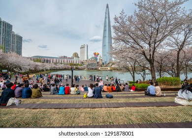 SEOUL, SOUTH KOREA - APRIL 10, 2018 : Many people picnic and looking view of Cityscape of Seoul downtown city with cherry blossom in Seokchon Lake and sakura around lake at Seoul city, South Korea