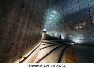 SEOUL, SOUTH KOREA - APRIL 11, 2018 : Young man traveler standing on stair of the Dongdaemun Design Plaza (DDP) at night in Seoul city,South Korea.