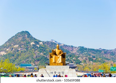 Seoul, South Korea - April 17, 2015: Tourists walking around centered King Sae Jong Dae Wang statue in front of Bugaksan mountain in city center, downtown on a blue sky day