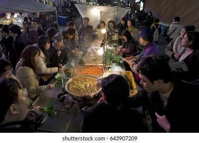 Seoul, South Korea – April 17, 2010 : Myeong-dong is one of the key shopping and  affordable street food districts .People are eating Tteokbokki Spicy Rice Cakes and fishcake served with hot broth.
