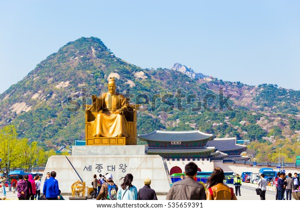 Seoul, South Korea - April 17, 2015: Tourists walking around King Sae Jong Dae Wang statue in front of Gyeongbokgung Palace and Bugaksan mountain in downtown on a blue sky day. Horizontal