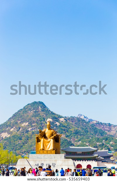 Seoul, South Korea - April 17, 2015: Tourists walking near King Sae Jong Dae Wang statue in front of Gyeongbokgung Palace and Bugaksan mountain in downtown city center on blue sky day. Vertical