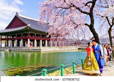Seoul, South Korea - April 4, 2018 : View of a couple dressing Korean costume and taking pictures with the cherry blossoms and the Gyeongbok Palace in the background in Seoul on April 4, 2018.