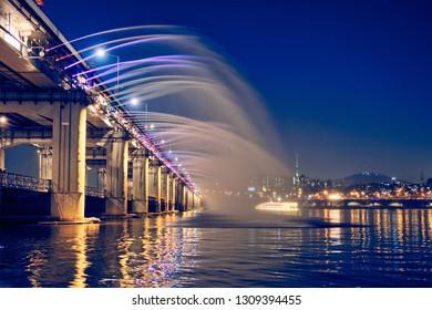 SEOUL, SOUTH KOREA - APRIL 7, 2017: Banpo Bridge Rainbow Fountain tourist landmark on Han river illuminated at night, Seoul, South Korea