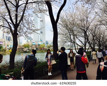 Seoul, South Korea, April 9, 2017, Hundreds of people gathers around Seokchon lake and Lotte world tower which is one of the cherry blossoms spots in Seoul, Korea