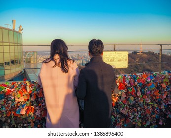 SEOUL, SOUTH KOREA - APRIL29, 2019 : love couple with Many colorful Padlock with the name and love text in Seoul Tower on Namsan mountain during winter, Seoul, South Korea