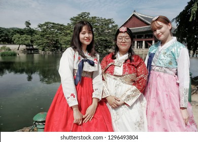 SEOUL, SOUTH KOREA - August 20, 2018: Asian women dressed in a traditional Korean costume, in the Gyeongbokgung Palace. Gyeonghweru Pavilion reflected in a lake.