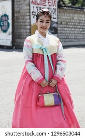 SEOUL, SOUTH KOREA - August 20, 2018: Asian girl dressed in a traditional Korean costume, in the Gyeongbokgung Palace.