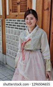 "SEOUL, SOUTH KOREA - August 20, 2018: Asian girl dressed in a traditional Korean costume, in the old village "" Hanok "" with old traditional houses."
