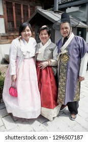 "SEOUL, SOUTH KOREA - August 20, 2018: Asian people dressed in a traditional Korean costume, in the old village "" Hanok "" with old traditional houses."