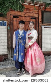 "SEOUL, SOUTH KOREA - August 20, 2018: Asian couple dressed in a traditional Korean costume, in the old village "" Hanok "" with old traditional houses."