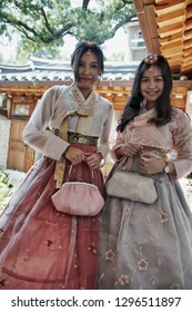 "SEOUL, SOUTH KOREA - August 20, 2018: Asian girls dressed in a traditional Korean costume, in the old village "" Hanok "" with old traditional houses."