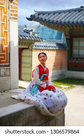 SEOUL, SOUTH KOREA - August 20, 2018: young asian girl with traditional dress in Gyeongbokgung palace with old facades houses.