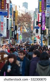 Seoul, South Korea: Christmas lights at Myeongdong shopping street, people tourists walking shopping the neighborhood.