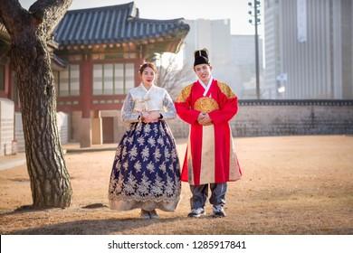 Seoul, South Korea - December 23, 2018: Men and women dressed in hanboks in traditional walking clothes, Gyeongbok Palace, Seoul, South Korea