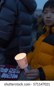 SEOUL, SOUTH KOREA - DECEMBER 3, 2016: A young boy holds a makeshift candle as he joins his parents in protest demanding the resignation of president Park Geun-hye
