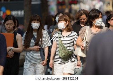 SEOUL, SOUTH KOREA - JUN 19, 2015: A tourist wearing a mask for protect from Mers virus in South Korea, at Seoul Market Myeong-dong Virus MERS, which has no known cure or vaccine.