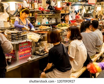 Seoul, South Korea - June 21, 2017: People eating tasty food and drink at Gwangjang Market in Seoul. One of the most popular street food place where you can buy kimbap, teokbokki, bibimbap, kimchi.