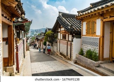 Seoul, South Korea - June 29, 2018:  Tourists dressing in traditional Korean Hanbok while walking in historic Korean style neighborhood in Bukchon Hanok village in Seoul, South Korea.