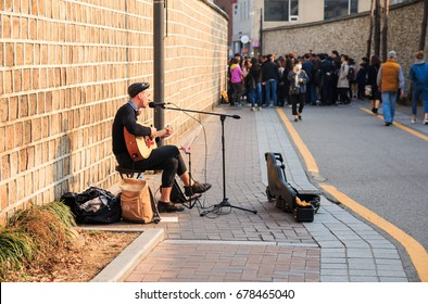 Seoul, south Korea - Mar 19, 2017: A young man busking with guitar and microphone in Insadong street.