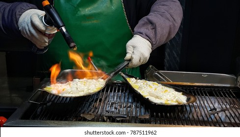 Seoul, South Korea - March 3, 2017 Flame of scallops ~ A kind of street snack in Seoul. Chopped fresh scallops, with cheese on top, are cooked by a flamethrower. Customers may see the whole process.