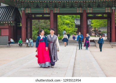 SEOUL, SOUTH KOREA - MAY 1, 2016: A happy-looking and smiling Korean native couple dressed in the traditional Hanbok seen walking around the palace's quarters in Changdeokgung Palace.