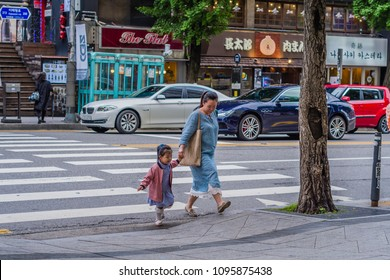 Seoul, South Korea; May 18, 2018: Young mother holding hand of her small daughter crossing street at crosswalk in itaewon.