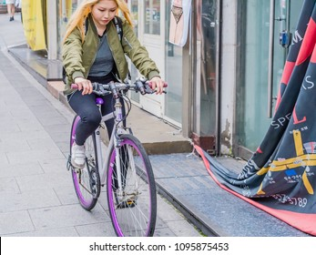 Seoul, South Korea; May 18, 2018: Young Asian woman with blonde hair riding bicycle on sidewalk in Itaewon.