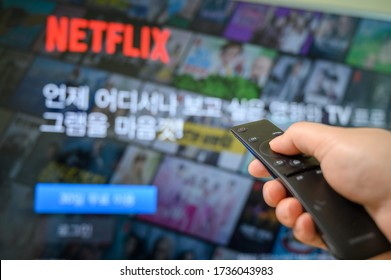 Seoul, south Korea - May 20, 2020: Man's hand operating remote control towards television with Netflix screen on.