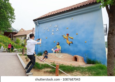 Seoul, South Korea - May 24, 2014_Dad captures photo of his kids with cute wall at Petite France, a French-style theme park that was constructed in July 2008 in Gyeonggi Province, South Korea.