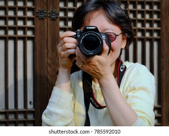 SEOUL, SOUTH KOREA - MAY 24, 2013: Middle-aged Korean American female street photographer (tourist) takes aim with her Canon DSLR camera in downtown Seoul, on May 24, 2013.