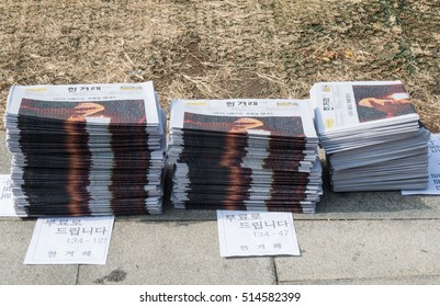 Seoul, South Korea, Nov 12th 2016: News papers and placards were distributed for free at Gwanghwamun square before the rally  to demand the ouster of President Park Geun-hye.