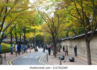 SEOUL, SOUTH KOREA : NOVEMBER 01, 2017 - People enjoying colorful autumn scenery along the Deoksugung stonewall street.