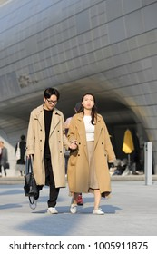SEOUL, SOUTH KOREA – NOVEMBER 4, 2017: Young couple in stylish trenchcoats walking along the Dongdaemun Design Plaza in Seoul's fashion district, on November 4, 2017 in Seoul.