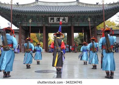 SEOUL, SOUTH KOREA - NOVEMBER 8, 2015: Armed guards in traditional costume guard the entry gate at Deoksugung Palace, a tourist landmark, in Seoul. November 8, 2015 Seoul, South Korea