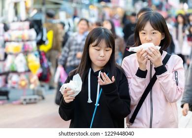 SEOUL SOUTH, KOREA - OCT 21,2018 : Woman eating food in Hongdae(Hongik University) shopping street. Hongdae is a shopping cultural street for young people in Seoul.