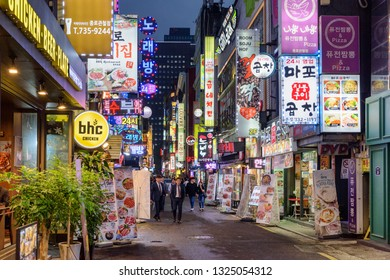 Seoul, South Korea - October 10, 2017: Amazing evening view of narrow street at downtown. Tourists and residents walking along bars and restaurants. Seoul is a popular tourist destination of Asia.